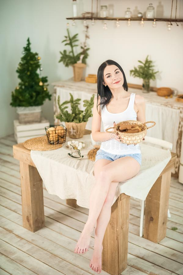 Young woman at home in the morning in the kitchen in light colors. The girl eats cookies, opens the refrigerator, prepares ginger. Cookies. Morning breakfast in stock images