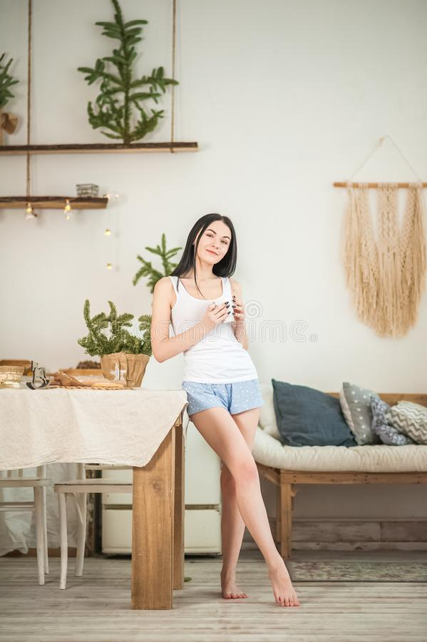 Young woman at home in the morning in the kitchen in light colors. The girl eats cookies, opens the refrigerator, prepares ginger. Cookies. Morning breakfast in stock image