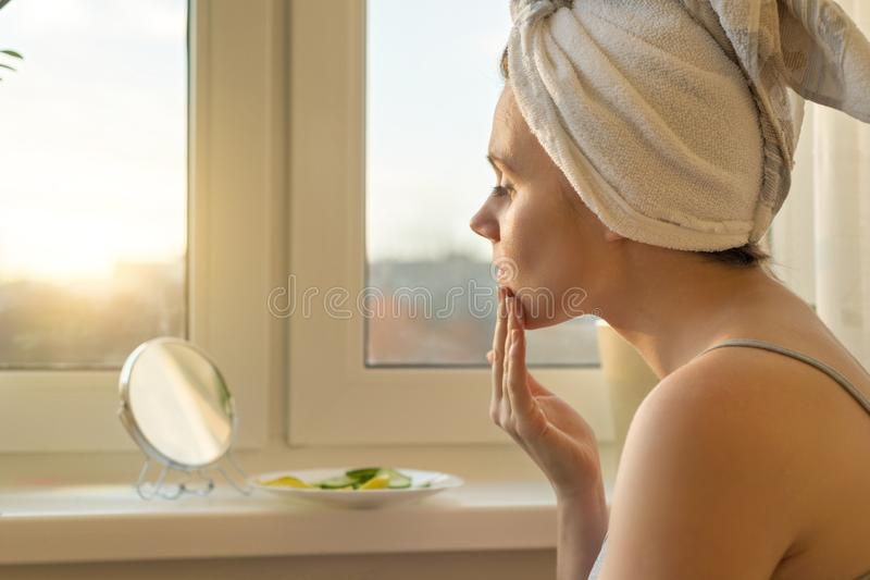 Young woman at home near the window looking in mirror, caring for face with cream and making mask with cucumber and lemon, towel royalty free stock image