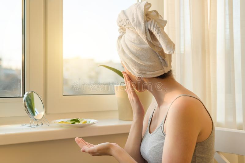 Young woman at home near the window looking in mirror, caring for face with cream and making mask with cucumber and lemon, towel royalty free stock images