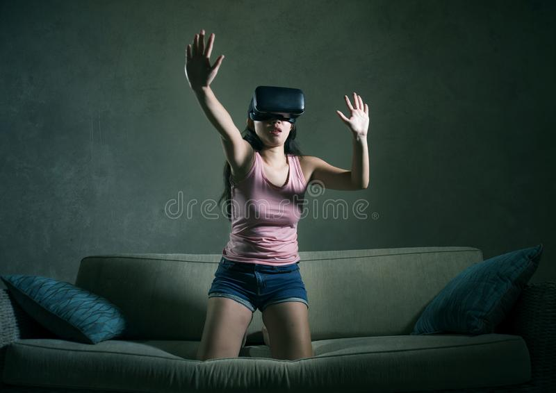 Young woman at home sofa couch playing video game using VR virtual reality goggles watching in 3 dimension enjoying curious having. Young woman at home sofa royalty free stock image