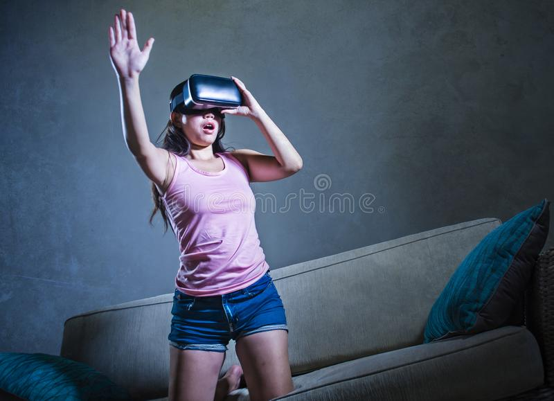 Young woman at home sofa couch playing video game using VR virtual reality goggles watching in 3 dimension enjoying curious having. Young woman at home sofa royalty free stock images