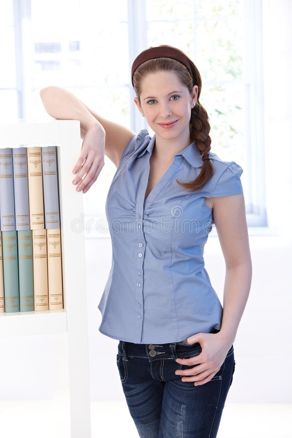 Download Young Woman At Home Standing By Bookshelf Stock Photo - Image of image, exercise: 20339402