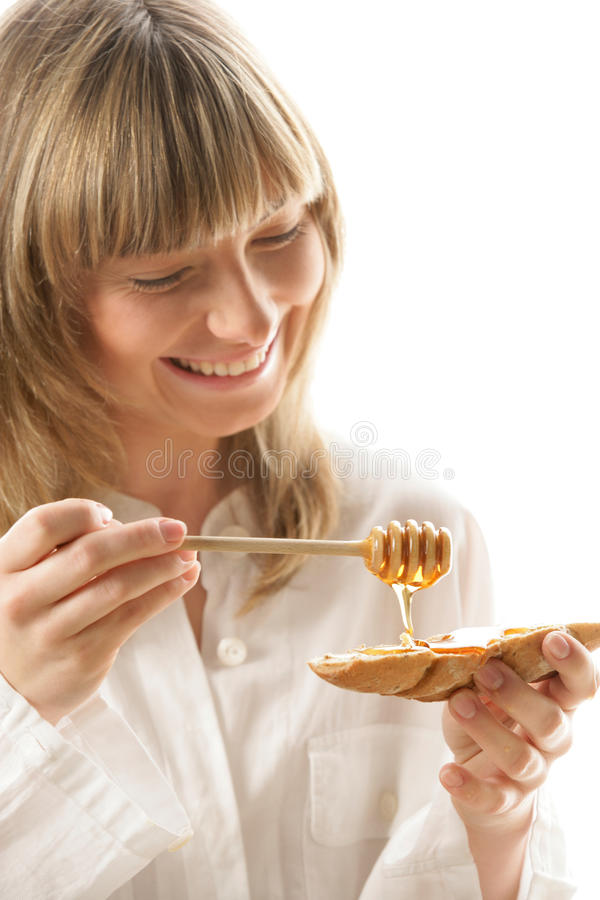 Young woman with honey and bread stock images