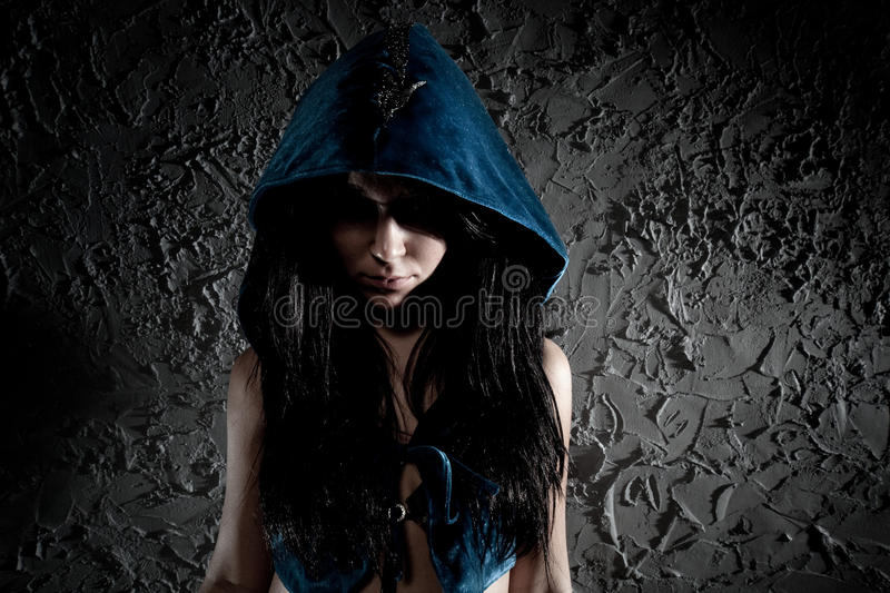 Young woman with hood on head. Dark contrast colors stock photography