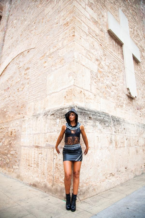 Young woman with hood and leather clothes poses in the corner of a church with a cross in the background royalty free stock images