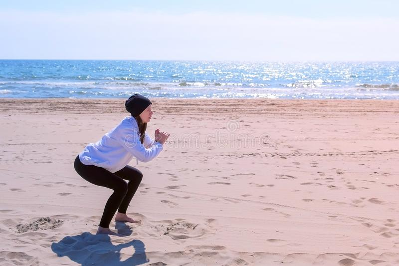 Woman makes squats on sea sand beach fitness outdoor sport exercises training. Young woman in hoodie, hat and leggings on sea sand beach. She does squats royalty free stock photo