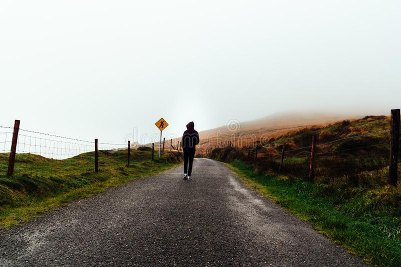 Young woman on hoodie walks on misty road royalty free stock images