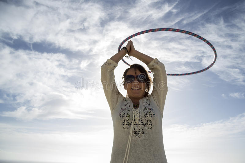 Young woman Hoola Hooping on the beach. A young woman/ girl, holla hooping on the beach on a sunny day stock photo