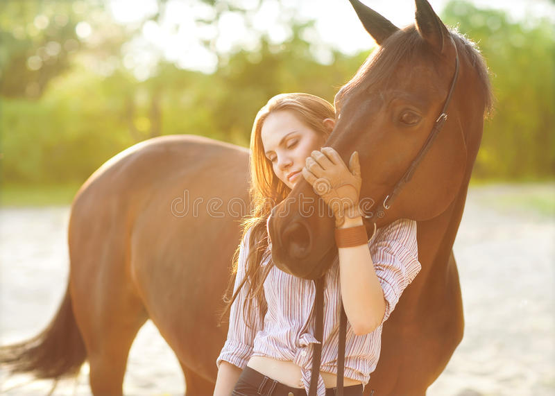 Young woman with a horse. In park near the river. Backlight stock photos