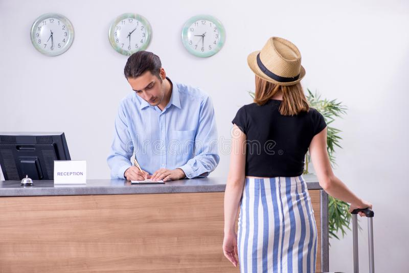 Young woman at hotel reception. The young women at hotel reception stock photo