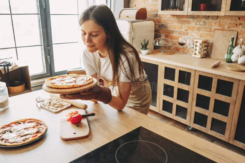 Young woman housewife baking pizza for her family stock photography
