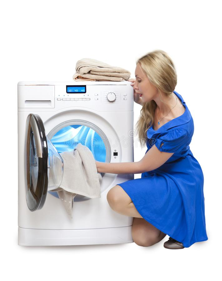 The young woman, the housewife, in a blue dress puts linen in the washing machine royalty free stock images