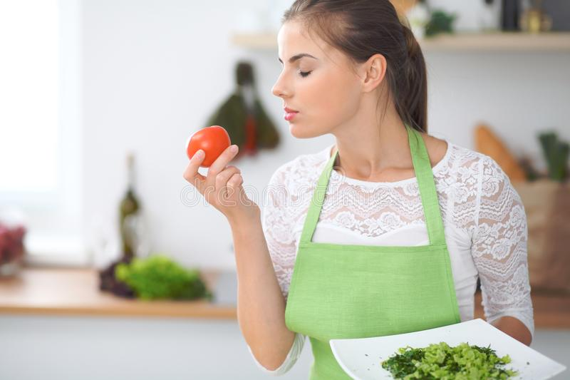 Young woman housewife cooking in the kitchen. Concept of fresh and healthy meal at home.  royalty free stock photos