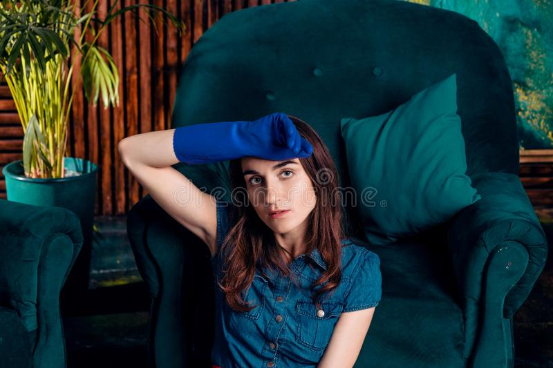 Young woman housewife tired after cleaning the apartment, sitting on the floor wipes her forehead with the back royalty free stock photos