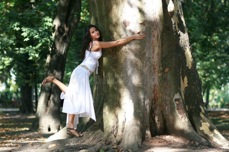 Young woman hugging ancient tree. Beautiful girl loving and giving hugs to large tree trunk stock photo