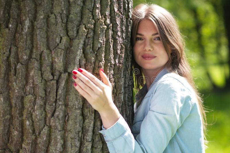 Woman hugging a big tree. Young woman hugging a big tree, love nature concept stock image