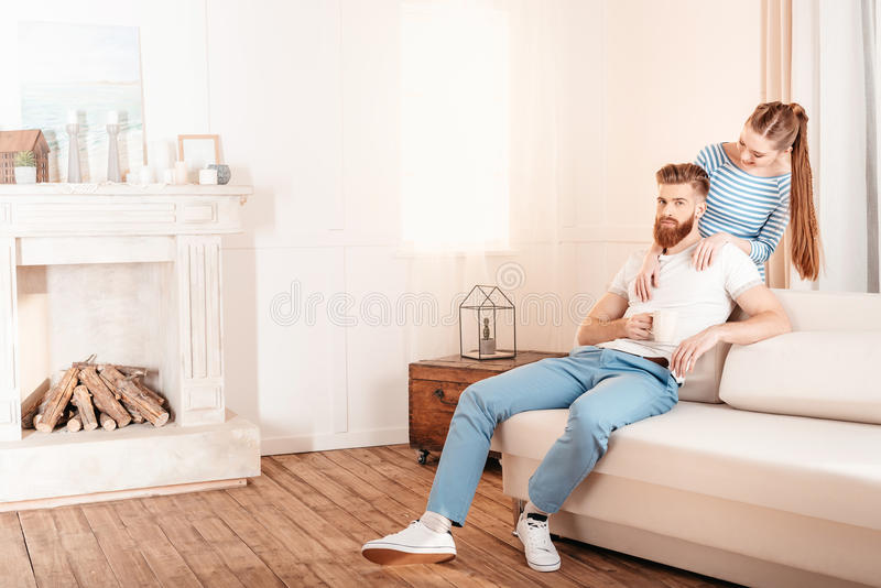 Young woman hugging handsome bearded man sitting on sofa at home stock images