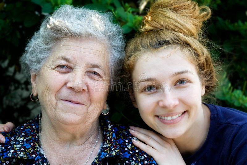 Young woman hugging her grandmother. Portrait of young woman hugging her grandmother royalty free stock photo