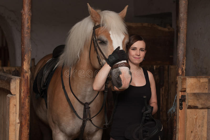 Young woman hugging her horse in stable. stock photos