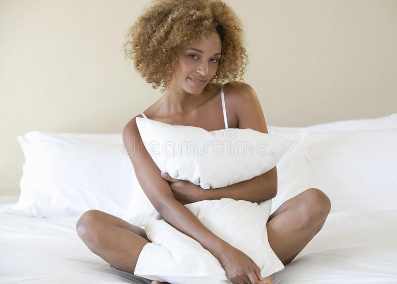 A young woman hugging a pillow stock photography