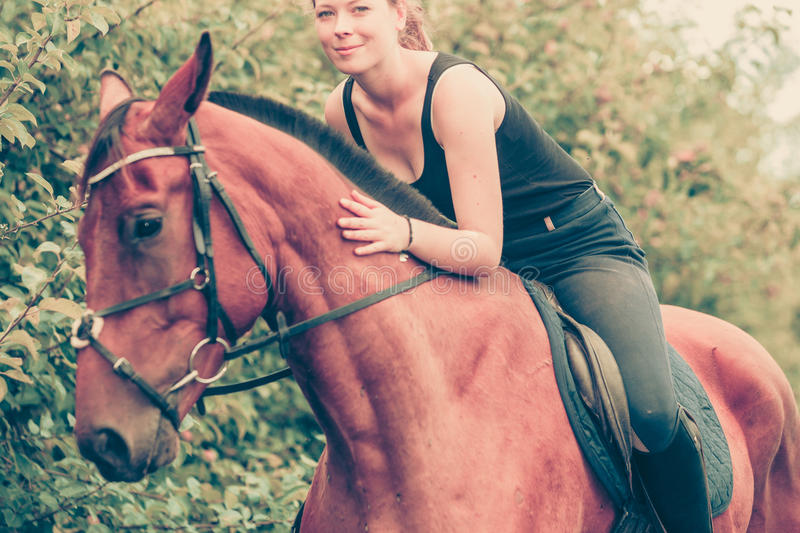 Young woman hugging and sitting on horse. Animal, horse riding concept. Young woman sitting on horse and hugging it royalty free stock photos