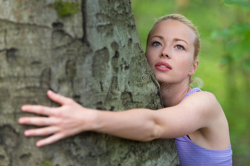 Young woman hugging a tree. Relaxed young lady embracing a tree receiving life energy from the nature royalty free stock photography
