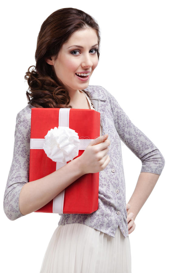 Young woman hugs a gift wrapped in red paper