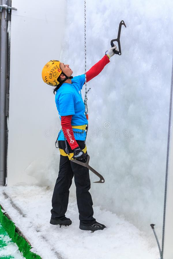 Young woman ice climber about to climb ice wall at ice climbing side-show attraction in Olympic royalty free stock image