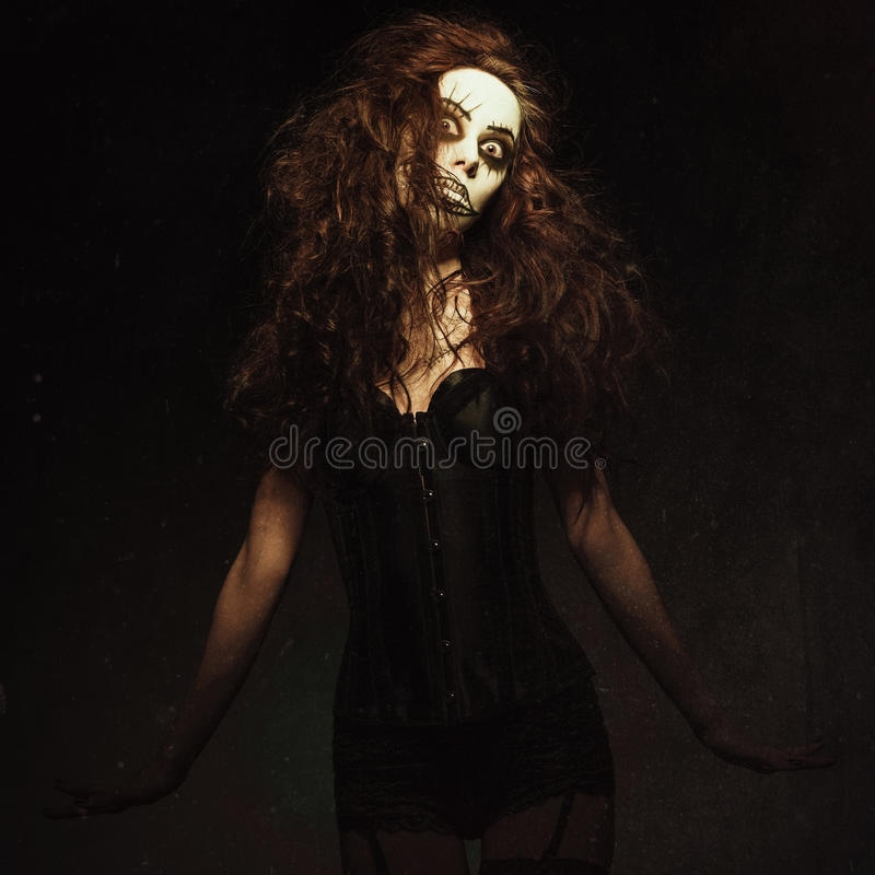 Young woman in the image of sad gothic freak clown. Grunge texture effect. Young woman in the image of a sad gothic freak clown. Grunge texture effect royalty free stock photography