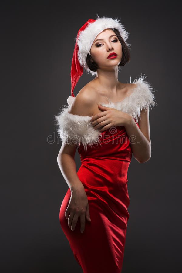 Free Young Woman In A Red Skirt And Santa Claus Hat On A Light Background Celebrates Christmas Stock Images - 104490564