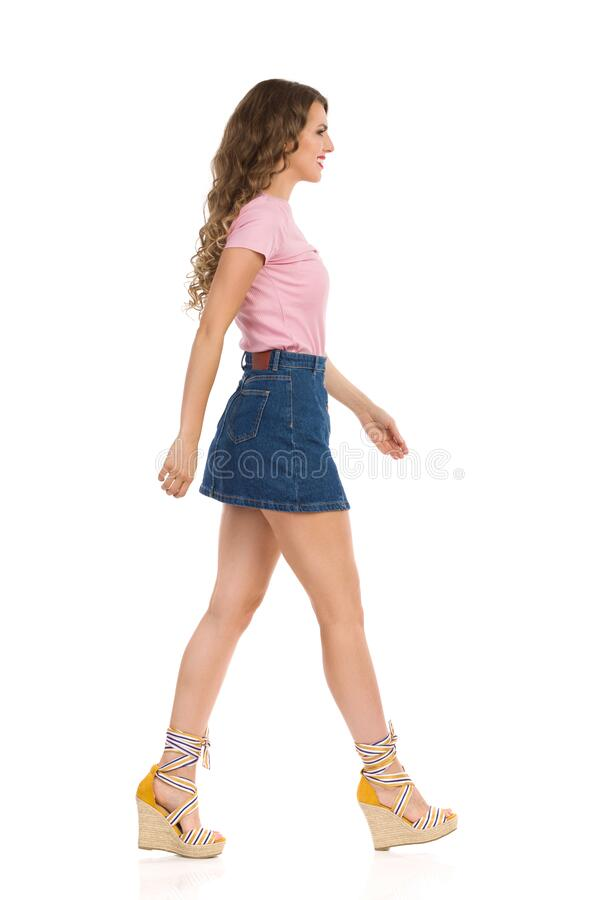 Free Young Woman In Jeans Mini Skirt And Wedge Shoes Is Walking. Side View Royalty Free Stock Image - 188739196