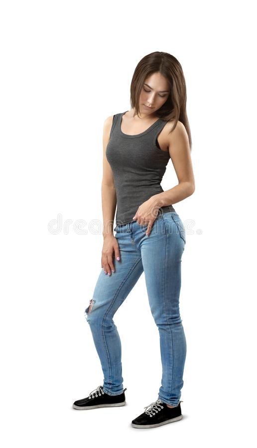 Free Young Woman In Sleeveless Top And Jeans Standing In Half-turn Looking Down Isolated On White Background. Royalty Free Stock Images - 143052159