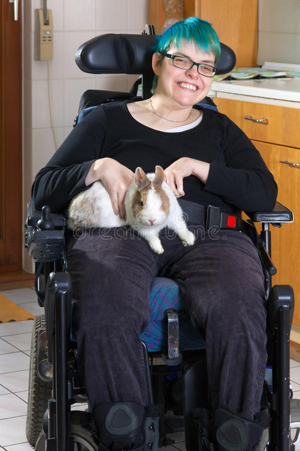 Young woman with infantile cerebral palsy. Young woman with infantile cerebral palsy due to birth complications confined to a multifunctional wheelchair royalty free stock image