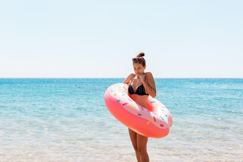 Young woman with inflatable ring cold shivering sad crossed arms black bikini swimsuit standing in sea water. Summer holidays and stock photos