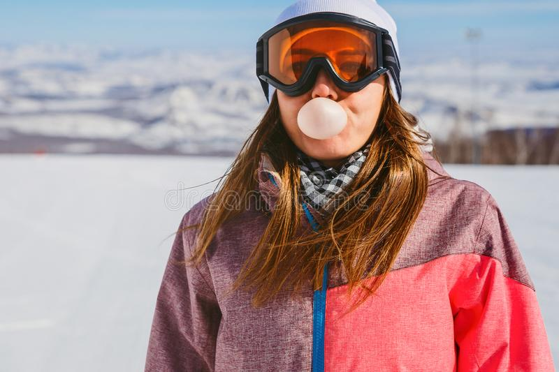 Young woman inflates big bubble gum. In the mountains in winter stock images