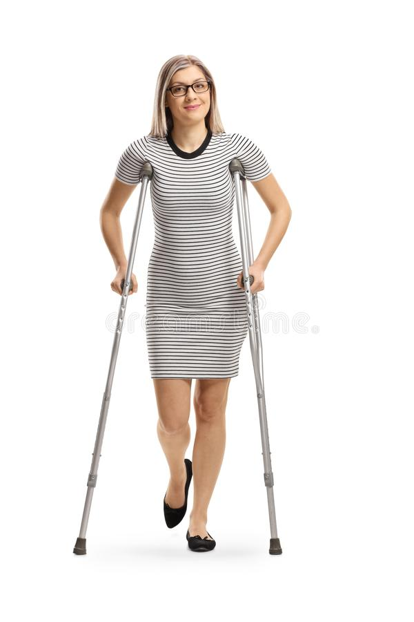 Young woman with an injured leg walking with crutches stock photography