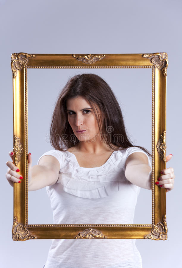Young woman inside a picture frame. Young beautiful woman inside an antique picture frame (isolated on gray royalty free stock image