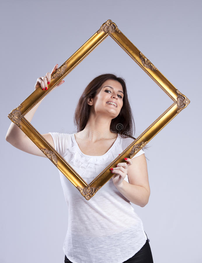 Young woman inside a picture frame. Young beautiful woman inside an antique picture frame ( on gray stock photography