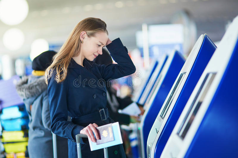 Young woman in international airport. Doing self check-in, stressed and concerned. Missed, delayed or canceled flight concept stock photography