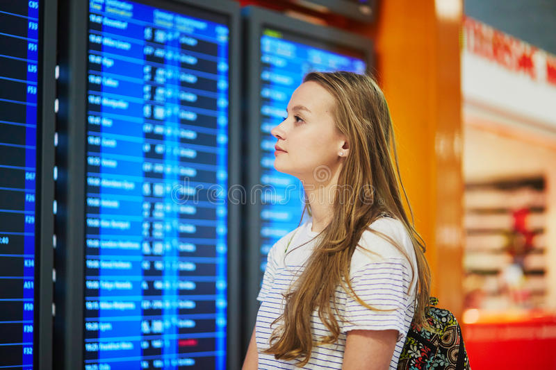 Download Young Woman In International Airport Looking At The Flight Information Board Stock Photo - Image: 83723730