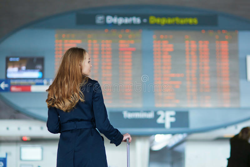 Young woman in international airport. Looking at the flight information board, checking her flight stock photo