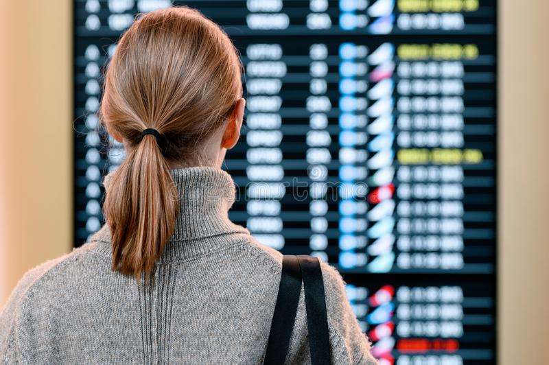 Young woman in international airport looking at the flight information board royalty free stock photos