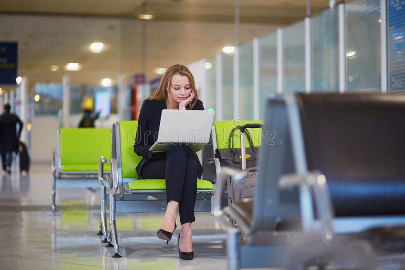 Woman in international airport working on laptop stock photography