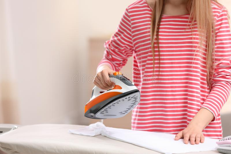 Young woman ironing clean laundry on board indoors, closeup. Space for text stock images
