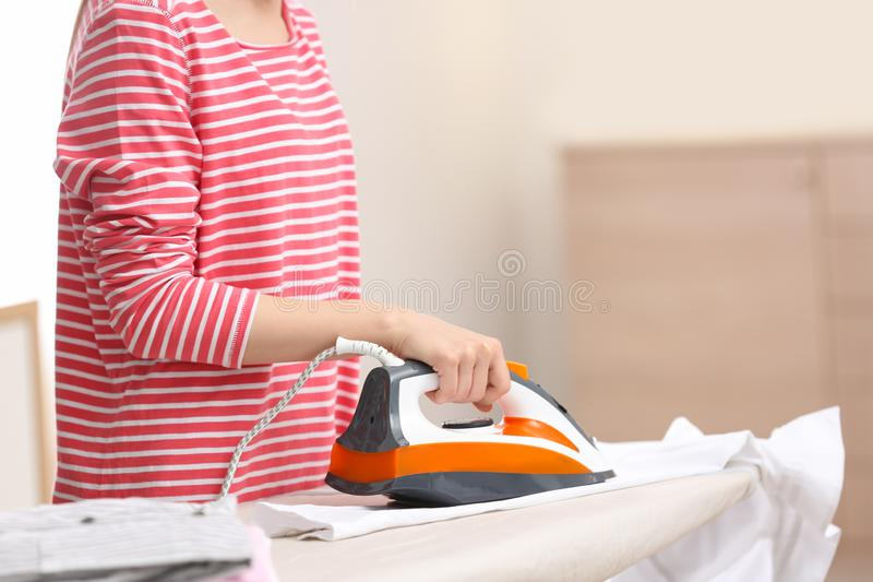 Young woman ironing clean laundry on board indoors, closeup. Space for text royalty free stock photography