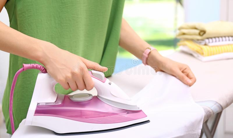 Young woman ironing clean laundry indoors, closeup. Space for text stock photo