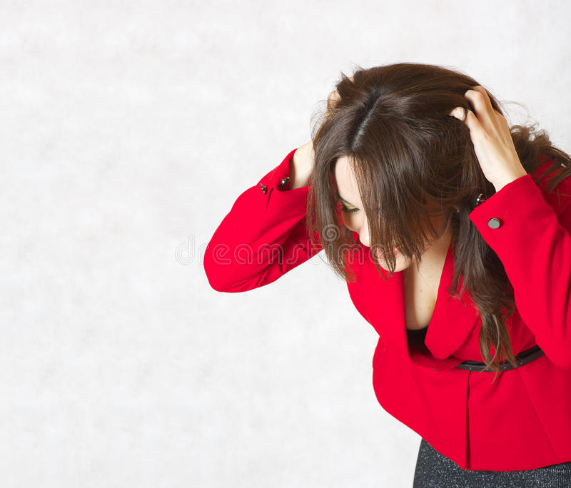 A young woman itches her head. A young woman between 30 and 40 years old dressed in a classical red jacket itches her head skin stock photos