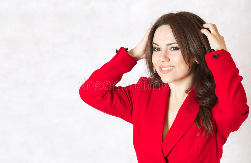 A young woman itches her head. A young woman between 30 and 40 years old dressed in a classical red jacket itches her head skin stock image