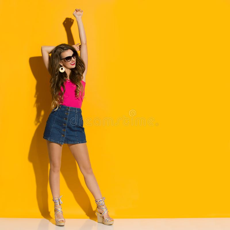 Young Woman In Jeans Mini Skirt, Magenta Top And Wegdes Is Standing With Arms Raised And Looking Away. Beautiful young woman in jeans mini skirt, magenta top and royalty free stock photo